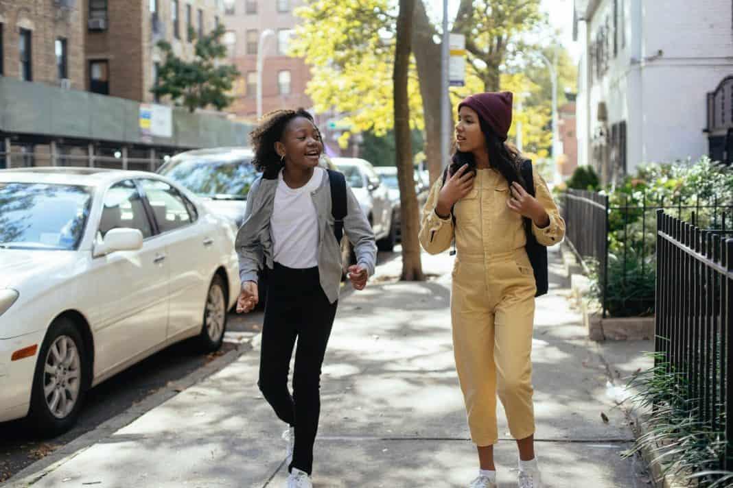 Fotografia com fundo claro de duas crianças caminhando em espaço urbano relacionado à cidades inteligentes