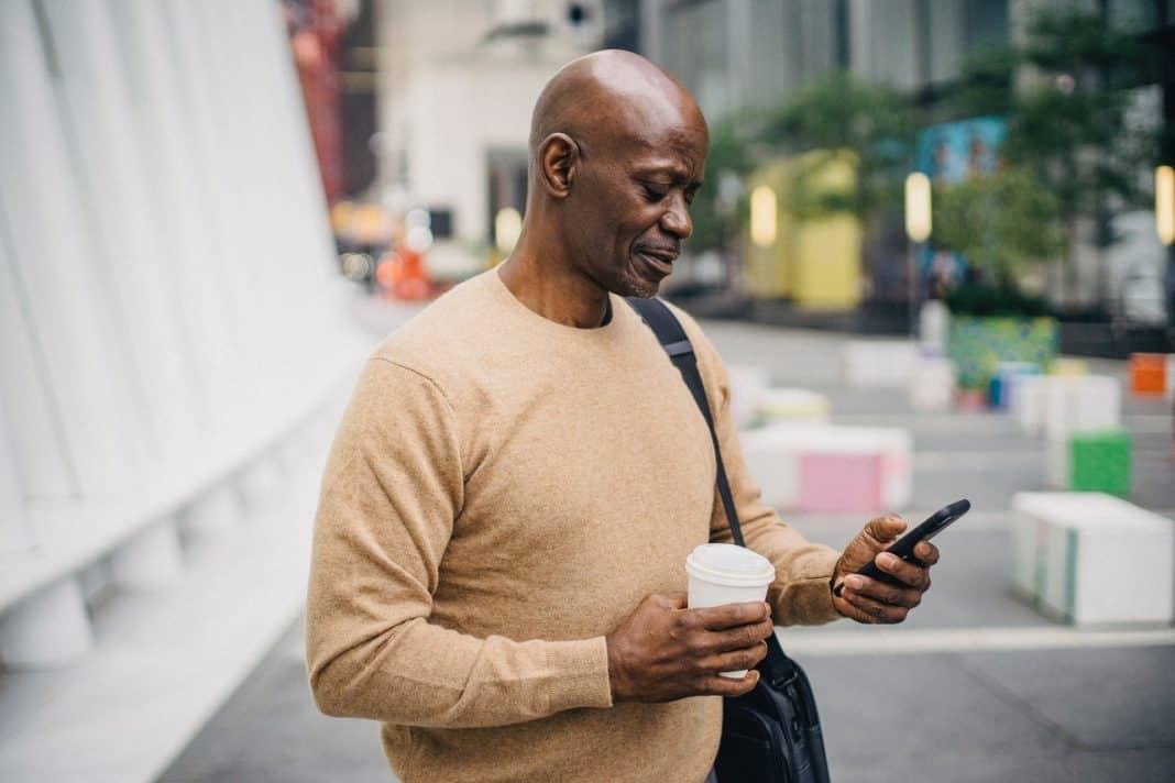 Fotografia de home com celular em cidade em alusãoà amizade entre membros da cidade