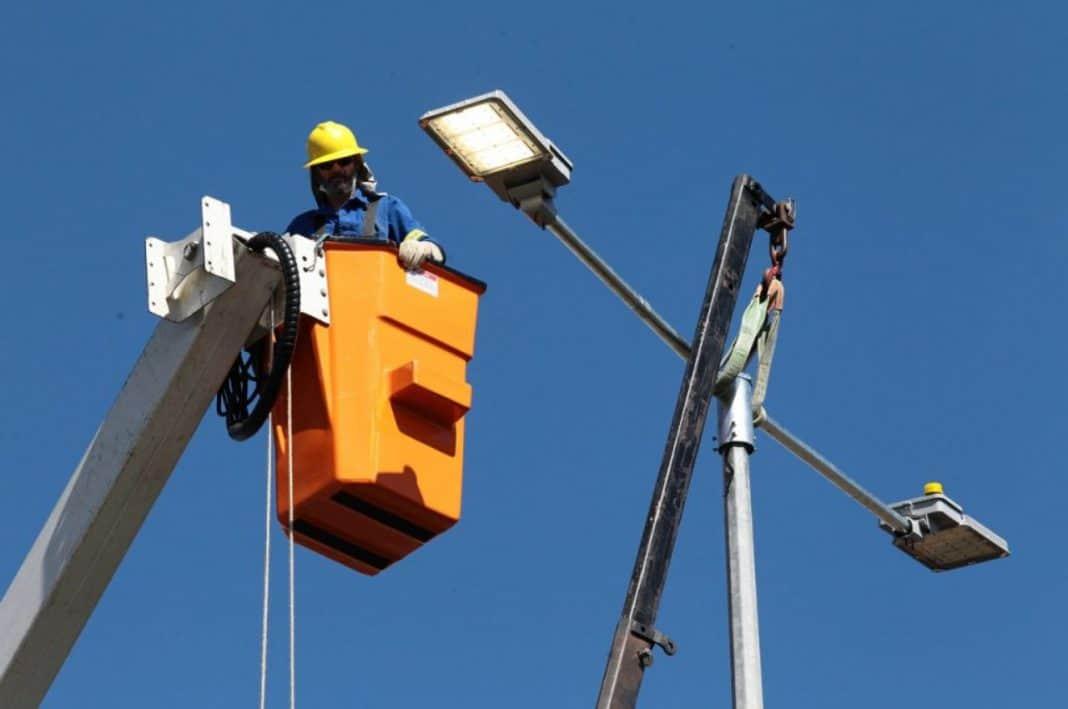 Fotografia de profissional trabalhando na rede de iluminação pública em licitação