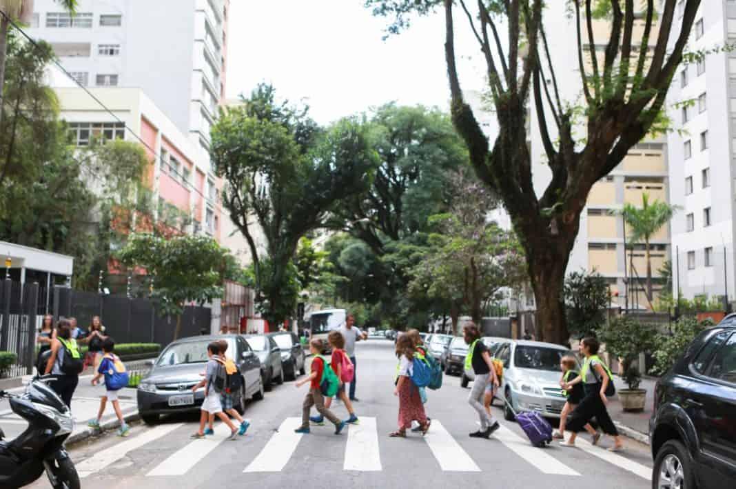 Fotografia de pessoas atravesando na faixa de pedestres em referência à mobilidade na escola