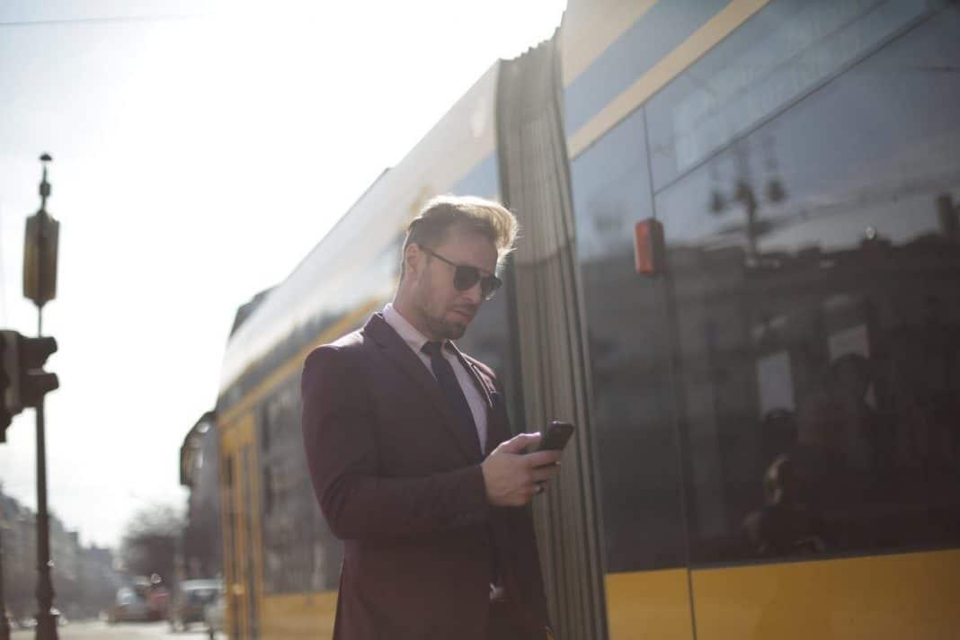 Fotografica de homem com celular ao lado de ônibus relacionando a mobilidade e universidades
